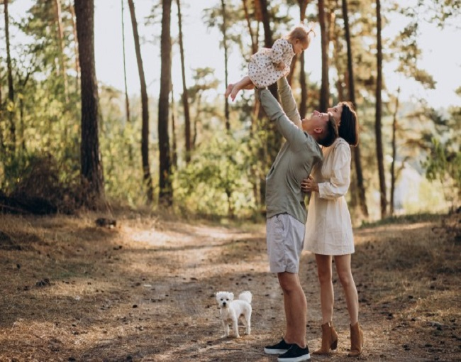 Young family with cute little daughter walking in forest