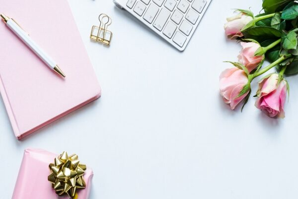 Flat lay of office desk with pink flowers, notebook and gift